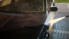 El hombre, trabajador, lava el coche T?nel de lavado usando el chorro de agua de alta presi?n almacen de video