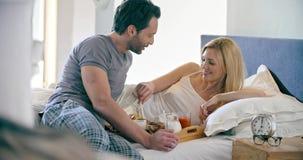El hombre trae el desayuno italiano a la mujer en cama y la consumición Los pares por mañana del amor despiertan en casa en dormi almacen de video