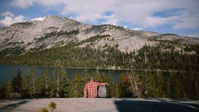 El hombre trasero de la visión camina para arriba para sentarse por una mujer y un beso cerca de la opinión del paisaje del lago  metrajes
