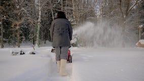 El hombre trasero de la visión limpia el fondo de la máquina de la retirada de la nieve de la nieve Forest In Winter metrajes