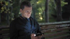 El hombre triste escribe un mensaje a su muchacha sin apoyo en una fecha que se sienta en la noche en el parque almacen de video