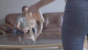 El hombre triste joven que se sienta en el sofá en el fondo mientras que esposa irreconocible que grita en él que lanza a una señ almacen de video