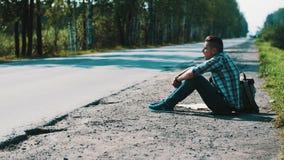 El hombre triste se sienta en el camino en campo hitchhiking El esperar Cigarrillo que fuma metrajes