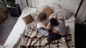 El hombre tuerce el globo, puntos de la mujer el destino para viajar Los pares multiétnicos en pijamas disfrutan y abrazan Cámara almacen de metraje de vídeo