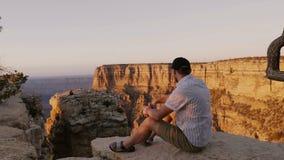 El hombre turístico adulto joven emocionado feliz se sienta en roca grande que mira paisaje increíble de la puesta del sol sobre  metrajes