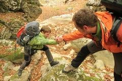 El hombre turístico ayuda alguien a subir la montaña Imagenes de archivo