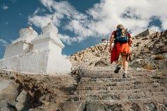 El hombre turístico sube para arriba las escaleras al lugar santo tibetano en Himalaya m Foto de archivo libre de regalías