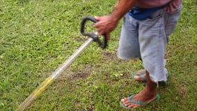 El hombre utiliza el cortacéspedes de hierba aprovisionado de combustible gasolina motorizado para arreglar el césped metrajes