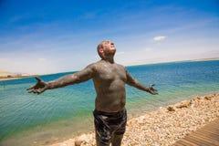 El hombre utiliza el fango terapéutico, gozando del sol fotos de archivo