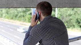 El hombre utiliza el teléfono al aire libre almacen de video