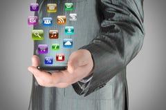 El hombre utiliza el teléfono elegante con los iconos Imagen de archivo