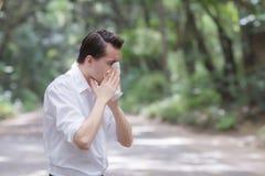 El hombre utiliza el estornudo del papel seda debido a tener alergia del polen fotografía de archivo libre de regalías