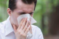El hombre utiliza el estornudo del papel seda debido a tener alergia del polen imagen de archivo