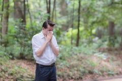 El hombre utiliza el estornudo del papel seda debido a tener alergia del polen fotografía de archivo