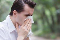El hombre utiliza el estornudo del papel seda debido a tener alergia del polen fotos de archivo