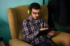 El hombre utiliza la tableta en el sofá en su hogar foto de archivo libre de regalías