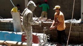 El hombre utiliza el mazo en el cincel de la albañilería de la palpitación sostenido por las pinzas del ayudante del trabajador almacen de metraje de vídeo
