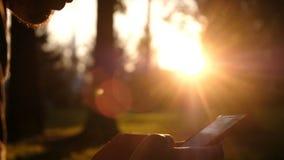 El hombre utiliza un smartphone e imprime un mensaje en la pantalla en el primer en el parque, movimiento de la puesta del sol de almacen de video