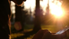 El hombre utiliza un smartphone e imprime un primer del mensaje en el parque en la puesta del sol, movimiento de la cámara metrajes