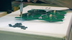 El hombre utiliza una herramienta para hacer la placa de circuito del PWB, cierre para arriba almacen de video