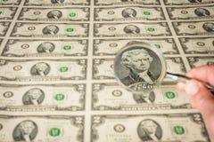 El hombre utiliza una lupa para examinar el dinero foto de archivo