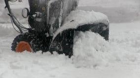 El hombre utiliza el ventilador de nieve para despejar nieve de la calzada metrajes