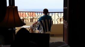 El hombre va al balcón con opiniones del mar almacen de metraje de vídeo