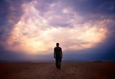 El hombre va al mar bajo el cielo nublado Imagenes de archivo