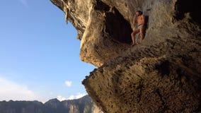 El hombre valiente del Adventurist está jugando Hapr descalzo en la cuesta de la cueva en el Krabi, Tailandia de la piedra caliza metrajes