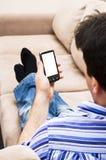 El hombre ve un smartphone en la opinión del retrato Fotos de archivo