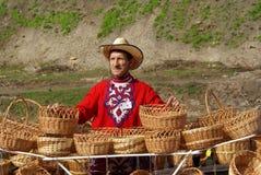 El hombre vende cestas de mimbre Imagen de archivo