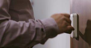 El hombre viene a la puerta del hotel y abre el sitio usando una llave electrónica electrónica Primer de la mano almacen de video