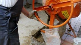 El hombre vierte el cemento de un mezclador concreto almacen de video