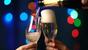 El hombre vierte el champán en dos vidrios en un fondo borroso de las luces de la Navidad multicoloras del centelleo metrajes
