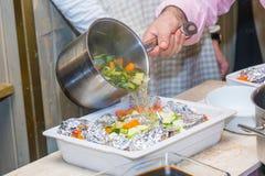 El hombre vierte la carne en caldo de la hoja concepto del rThe de cocinar Foto de archivo libre de regalías