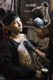 El hombre vietnamita joven que lleva un casquillo consigue un tatuaje en su pecho por el DMT del juego X en el festival 2018 del  imagenes de archivo