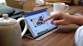 El hombre visita el sitio web del facebook en la PC de la tableta en un café almacen de video