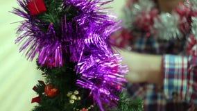 El hombre viste el pequeño árbol de navidad que brilla intensamente hermoso almacen de metraje de vídeo