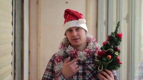 El hombre viste el pequeño árbol de navidad que brilla intensamente hermoso almacen de video