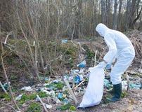 El hombre voluntario en la ropa protectora blanca recoge la basura Imágenes de archivo libres de regalías