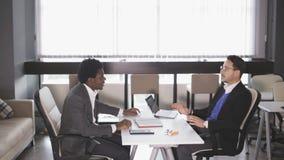El hombre y el afroamericano europeos sirven sentarse en butacas y negocian almacen de video