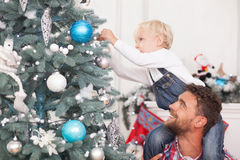 El hombre y el niño bonitos están adornando el árbol del Año Nuevo Imagen de archivo