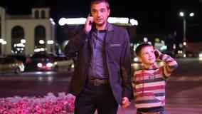 El hombre y el niño pasan con la noche de la ciudad y almacen de metraje de vídeo