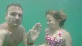 El hombre y la muchacha caucásicos se zambullen en el mar y agitar sus manos en la cámara debajo del agua almacen de metraje de vídeo