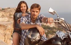 El hombre y la muchacha del motorista se sienta Imagenes de archivo