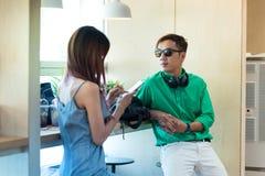 El hombre y la mujer asiáticos de los pares se sientan en cafetería Mirada del hombre hacia fuera apagado Foto de archivo libre de regalías