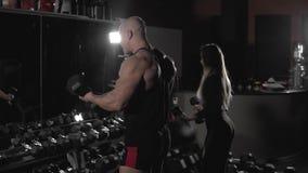 El hombre y la mujer atléticos hacen ejercicios de la pesa de gimnasia en el gimnasio oscuro en la cámara lenta almacen de metraje de vídeo