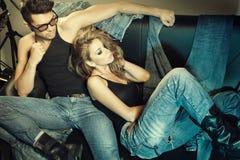 El hombre y la mujer atractivos se vistieron en la presentación de los pantalones vaqueros