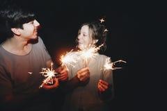 El hombre y la mujer caucásicos juntan jugar con la celebración de las bengalas y el concepto festivo del partido imágenes de archivo libres de regalías