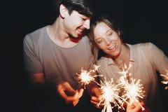 El hombre y la mujer caucásicos juntan jugar con la celebración de las bengalas y el concepto festivo del partido imagenes de archivo